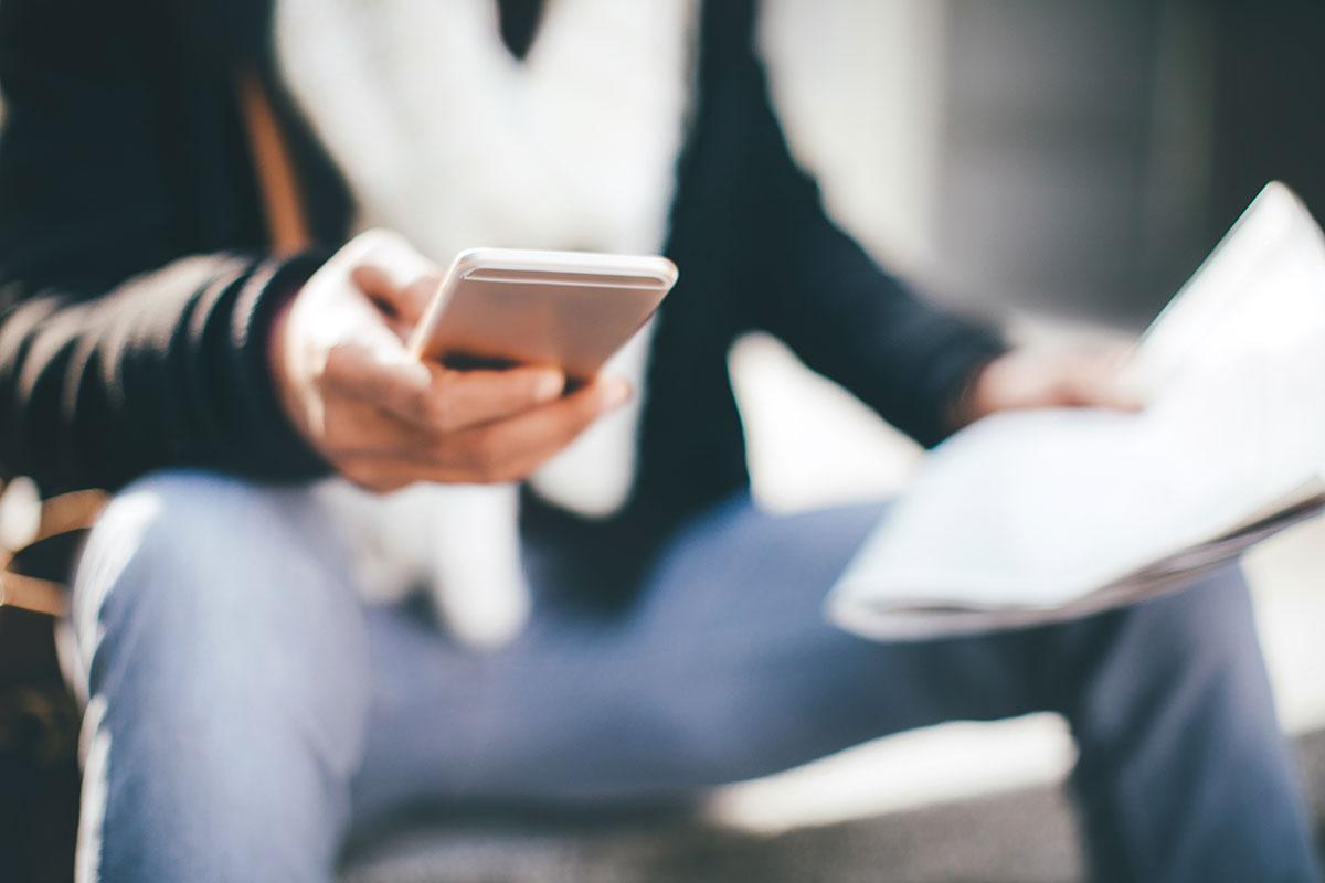 Jugendlicher hält ein Mobiltelefon
